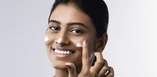 Beautiful and happy woman applying moisturizing cream on her face